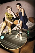 Zwei Frauen sitzen in einer Lounge, Martini-Glas in der Hand