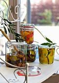 In Öl eingelegtes Gemüse in Einmachgläsern auf Tisch am Fenster