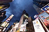 Low angle view of illuminated advertisements on building at Times Square in New York, USA