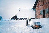 Outdoor cooking fire in front of snow-covered half-timbered house