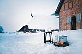 Feuerstelle vor schneebedecktem Fachwerkhaus