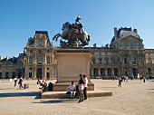 Facade of Louvre facade and tourist near statue in Paris, France