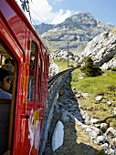 Passengers travelling in train between mountains at Alpnachstad, Lucerne, Switzerland