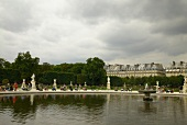 Tourists relaxing near water in Tuileries Garden in front of Roue de Paris, Paris, France