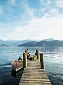 Tourists relaxing on jetty and boat moored in Lake Lucerne, Alps, Lucerne, Switzerland