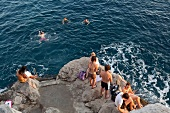 People enjoying bath and standing on rocks, Croatia