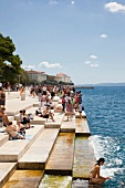 Tourists enjoying at Sea Organ on the promenade in Zadar, Croatia