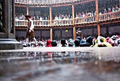 People in Auditorium of Globe Theatre during rain in London Borough of Southwark, UK