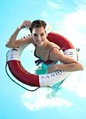 lächelnde Frau mit dunklen zusammen- gebundenen Haaren, Bikini, im Pool