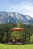 Loungers in garden of Hotel Schloss Elmau overlooking mountains, Upper Bavaria, Germany