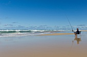 Fishermen sitting with fishing rod on beach, Fraser Island, Queensland, Australia