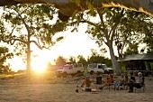People sitting around camp fire in Ormiston Creek, Alice Springs, Australia