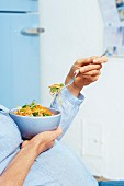 Schwangere Frau isst vegetarisches Wokgericht