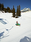 People having fun on snow tubing at Truebsee, Titlis, Uri Alps, Engelberg, Switzerland