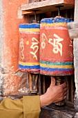 Hand holding prayer wheels at Jampey Lhakhang temple, Bhutan