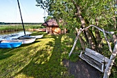 Boats moored and wooden swing in Galindia Mazurski Eden, Warmia Masuria, Poland