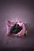 A black truffle mushroom on a piece of pink fabric