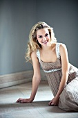 blonde Frau mit langem welligem Haar lacht, Abendkleid