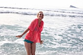 Frau im blauen Bikini, transparente Bluse in pink am Strand im Wasser