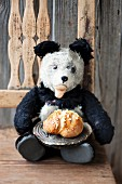 A teddy bear with a loaf of plaited sweet bread