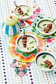 Sellerie-Kräuter-Rahmsuppe mit Lammspießen auf bunt dekoriertem Tisch