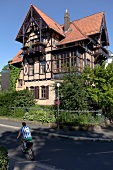 View of half-timbered villa with man cycling uptown, Kassel, Hesse, Germany