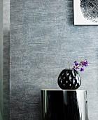 Schwarze Vase auf Ablagetisch vor grauer Wand