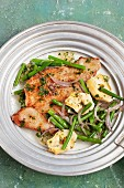 Veal escalope with artichokes, green beans and onions