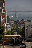 People travelling in tram and Bay bridge in background at San Francisco, California, US