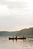 Three people sailing canoe in Breiter Luzin lake, Mecklenburg, Germany