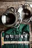 Stack of stainless steel bowls, pot and cutlery in pouch on table, elevated view