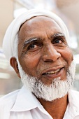 Close-up of senior man with beard and hat smiling, Oman