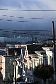 Power cables with houses and fog in San Francisco, California, USA