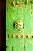 Close-up of green door with metal ring handle in Al Hamra, Oman