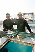 Two fisher man with fishes in front on Maghsil bay beach in Salalah, Dhofar, Oman