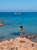 Woman in swimwear standing near Costa Paradiso in Sardinia, Italy