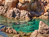 People swimming in sea near Costa Paradiso in Sardinia, Italy