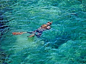 Person swimming in sea near Costa Paradiso in Sardinia, Italy