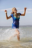 Frau, blond, rennt am Strand durch Wasser, lacht, Blilck nach unten