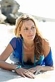 Frau liegt bäuchlings im Meer, am Strand im Samd
