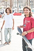 Two men in casuasl standing with skateboards on sidewalk, Beirut, Lebonan