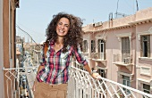 Portrait of Lara Chekerdjian with curly hair laughing in balcony, Beirut, Lebanon