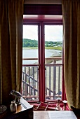 View of lake from boat house window with curtains, Laugharne, Carmarthenshire, Wales, UK