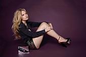 Frau sitz mit angewinkelten Beinen auf dem Boden, Shorts, Bluse