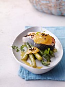 Baked salmon with asparagus and orange butter on plate in serving dish