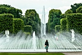 Woman in front of fountains at Royal Gardens in Herrenhausen Palace, Hannover, Germany