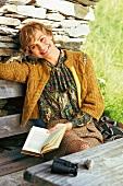 Frau lächelt verträumt, sitz auf einer Bank, stützt den Kopf ab, Buch