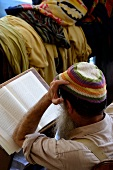 Rear view of man reading Torah with hands on head, Ari Ashkenazi Synagogue, Safed, Israel