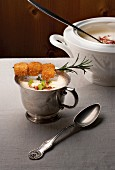 Potato soup with baked mountain cheese cubes in cup