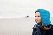 Frau im Mantel mit blauer Mütze an der frischen Luft, Nachdenken
